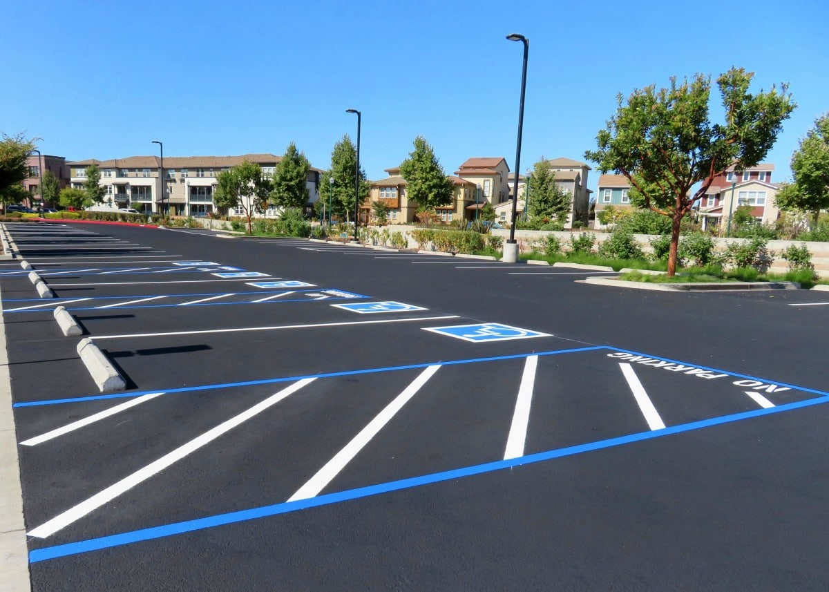 ADA Compliance Freshly resurfaced and repainted handicap parking space in a parking lot. The number of handicap spaces increases with the size of the lot, requiring roughly one handicapped spot per 25 spaces.